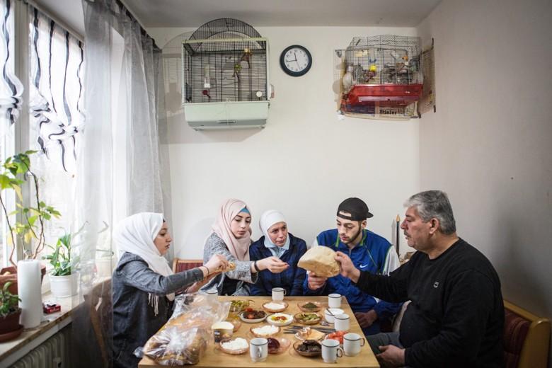 Bild der Familie am Küchentisch. Mutter Nusayba Qrqash (54) ist ausgebildete Laborantin, verbrachte mit ihrer Tochter Ruaa und ihrem Sohn Mohammad sieben Tage in einem Holzboot im Mittelmeer, bis sie ein deutscher Tanker rettete. Bis heute erträgt sie den Anblick von offenen Gewässern nicht. Obwohl es ihre vier Töchter und zwei Söhne in Sicherheit geschafft haben, bleibt Nusayba in Sorge - ihre Eltern leben noch immer in Damaskus. Wie baut man eine Zukunft, wenn man mit der Vergangenheit nicht abschließen kann?