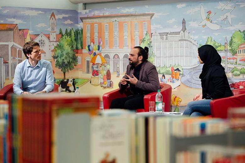 Bild von Friedolyn Schrey, Yamen Hussein und der Übersetzerin Marwa Amara auf der Bühne im Gespräch. Foto: Fritz Beck